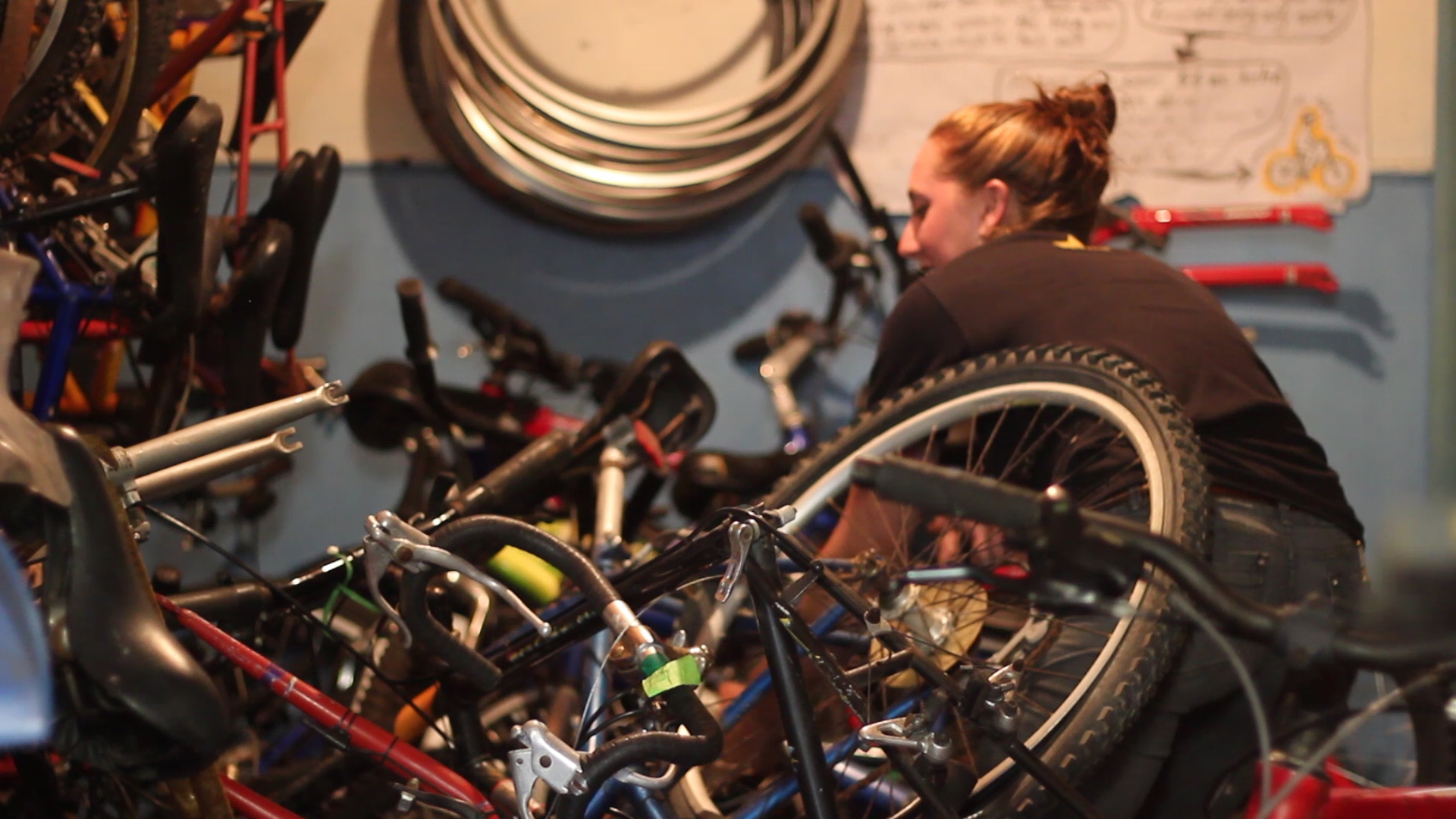 Volunteer mechanic, Sylvie Froncek, sifting through a pile of donated bicycles.